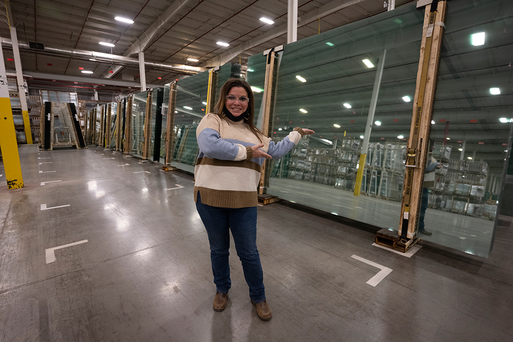Employee posing in front of sheets of glass